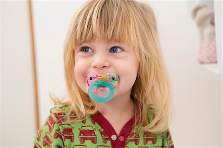 Portrait of  happy 2 year old girl with pacifier Stock Photo - Premium Royalty-Free, Code: 649-07647974