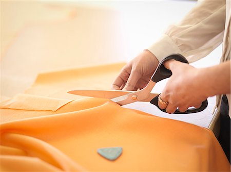 Fashion designer cutting cloth in fashion design studio, close up Stock Photo - Premium Royalty-Free, Code: 649-07648003
