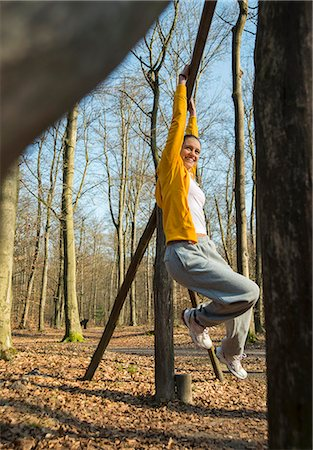 Young woman dangling from pole on forest assault course Stock Photo - Premium Royalty-Free, Code: 649-07648077