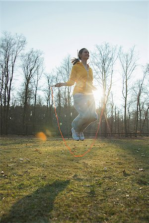day - Young woman exercising in field with skipping ropes Stock Photo - Premium Royalty-Free, Code: 649-07648096