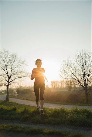 recreation - Young female runner, running at sunset Stock Photo - Premium Royalty-Free, Code: 649-07648099
