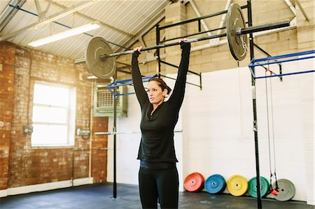 Woman lifting barbell in gym Stock Photo - Premium Royalty-Free, Code: 649-07648176
