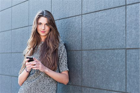 Young woman leaning against wall, holding smartphone Stock Photo - Premium Royalty-Free, Code: 649-07648184