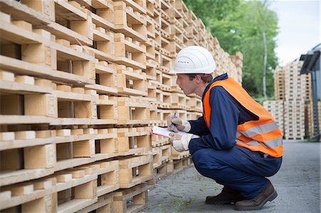 Young male worker pallet stock taking in timber yard Stock Photo - Premium Royalty-Free, Code: 649-07648217