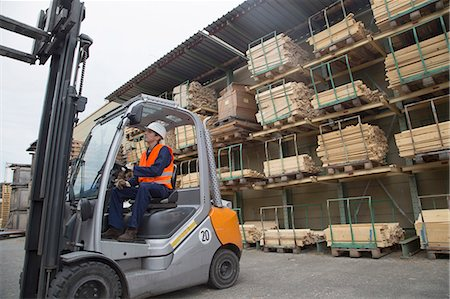 Young man driving a forklift truck in timber yard Stock Photo - Premium Royalty-Free, Code: 649-07648213