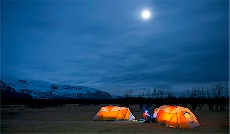 Mature woman sitting outside tent at night, Skaftafell, Vatnajokull National park, Iceland Stock Photo - Premium Royalty-Free, Code: 649-07648252