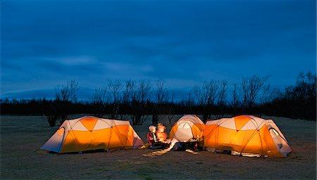 Three friends chatting outside tents at night, Skaftafell, Vatnajokull National park, Iceland Stock Photo - Premium Royalty-Free, Code: 649-07648253