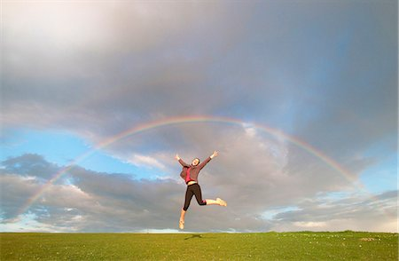 friluftsliv - Young female hiker jumping mid air below rainbow Stock Photo - Premium Royalty-Free, Code: 649-07648260