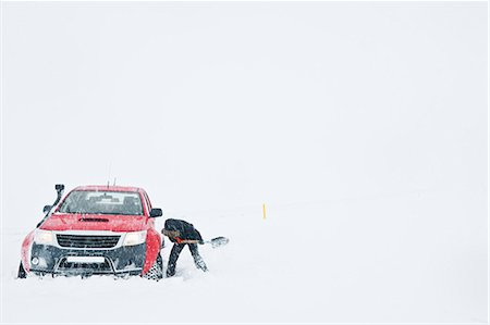 Mature woman digging out snow from stranded pick up truck, Fljotsheidi, North Iceland Stock Photo - Premium Royalty-Free, Code: 649-07648261