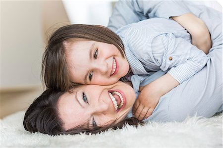 furry - Mother and daughter lying on rug, laughing Stock Photo - Premium Royalty-Free, Code: 649-07648303