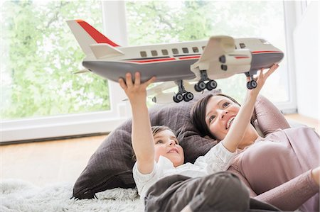 Mother and daughter playing with toy aeroplane Stock Photo - Premium Royalty-Free, Code: 649-07648314