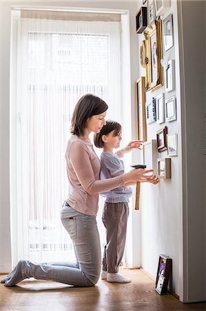 Mother and daughter hanging picture on wall Stock Photo - Premium Royalty-Free, Code: 649-07648317