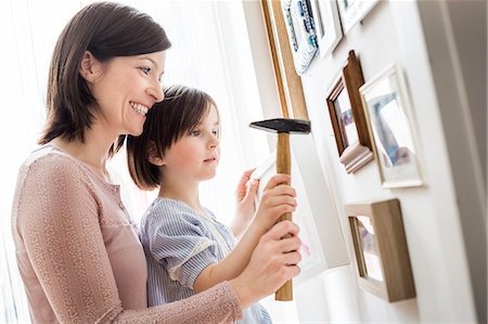 Mother and daughter hanging picture on wall Stock Photo - Premium Royalty-Free, Code: 649-07648318