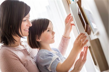 Mother and daughter adjusting picture Stock Photo - Premium Royalty-Free, Code: 649-07648319