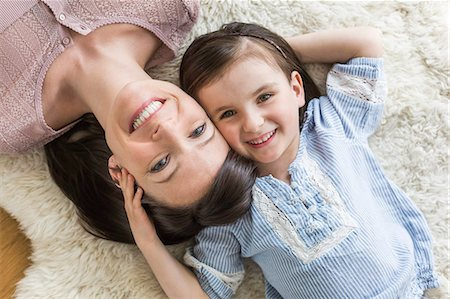 furry - Mother and daughter lying on fur rug, overhead view Stock Photo - Premium Royalty-Free, Code: 649-07648320