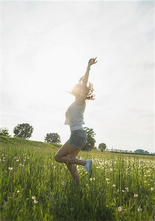 summer - Young woman jumping in field Stock Photo - Premium Royalty-Free, Code: 649-07648348