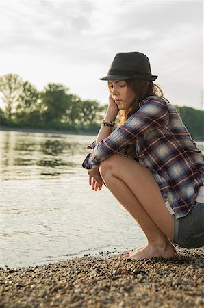 Young woman crouching by lake Stock Photo - Premium Royalty-Free, Code: 649-07648353