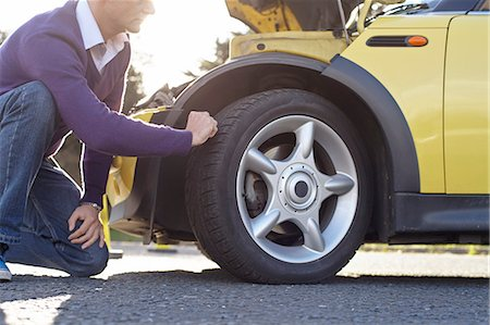 Man inspecting car tyre Stock Photo - Premium Royalty-Free, Code: 649-07648371