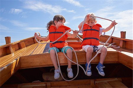 friendship - Two children sitting in boat, holding rope Stock Photo - Premium Royalty-Free, Code: 649-07648400