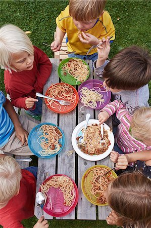 Overhead view of seven children eating spaghetti at picnic table Stock Photo - Premium Royalty-Free, Code: 649-07648415