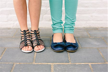 Close up of two sisters legs and footwear Stock Photo - Premium Royalty-Free, Code: 649-07648446