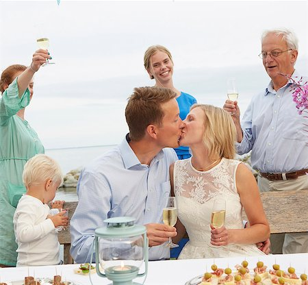 Mid adult couple kissing and making a toast with group of friends Stock Photo - Premium Royalty-Free, Code: 649-07648440