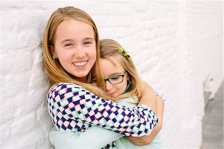 family  fun  outside - Two sisters holding hugging next to white wall Stock Photo - Premium Royalty-Free, Code: 649-07648443