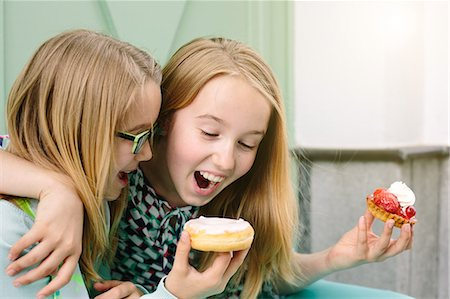 snack - Two happy sisters holding cakes Stock Photo - Premium Royalty-Free, Code: 649-07648450