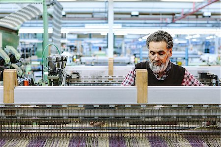 Male factory worker on weaving machine in woollen mill Stock Photo - Premium Royalty-Free, Code: 649-07648503