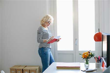 Mature woman at home writing in notebook Stock Photo - Premium Royalty-Free, Code: 649-07648524