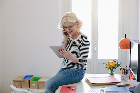 Mature woman at home using digital tablet and talking on phone Stock Photo - Premium Royalty-Free, Code: 649-07648526