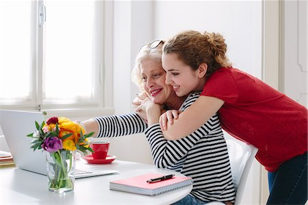 Mother and teenage daughter looking at laptop at home Stock Photo - Premium Royalty-Free, Code: 649-07648529