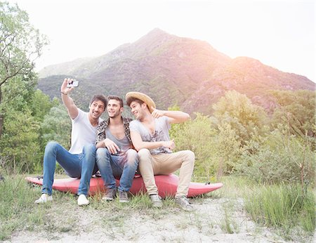 Three young men sitting on top of canoe, taking self portrait photograph Stock Photo - Premium Royalty-Free, Code: 649-07648551
