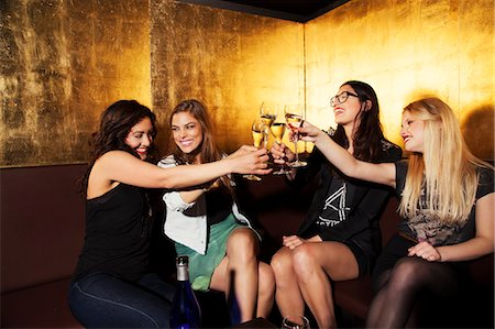 Four female friends toasting with wine in nightclub Stock Photo - Premium Royalty-Free, Code: 649-07648585