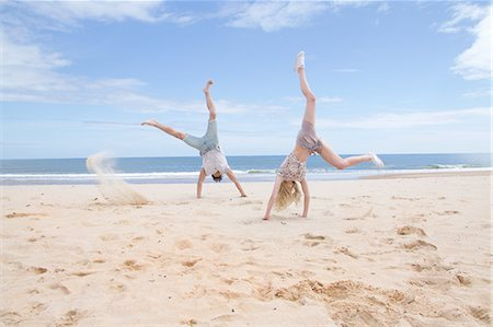 friendship - Young couple doing handstands on beach Stock Photo - Premium Royalty-Free, Code: 649-07648621