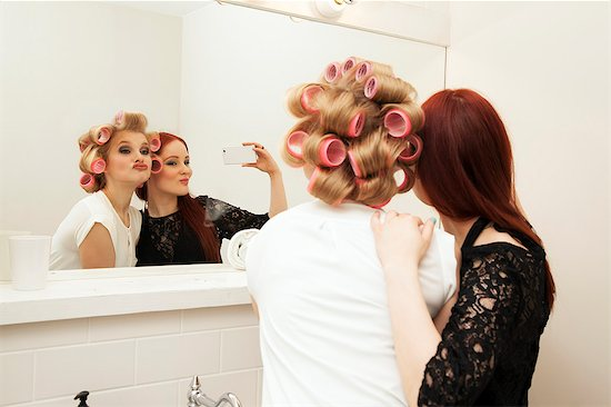 Young woman in curlers and friend taking selfie Stock Photo - Premium Royalty-Free, Image code: 649-07648652