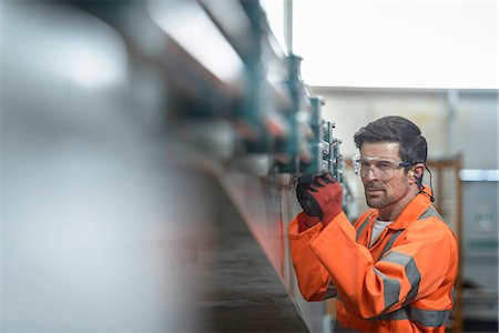 Engineer inspecting marine fabrication used for cable laying, close up Stock Photo - Premium Royalty-Free, Code: 649-07709977