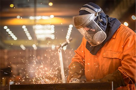 people working in factory - Worker grinding metal construction in marine fabrication factory Stock Photo - Premium Royalty-Free, Code: 649-07709972