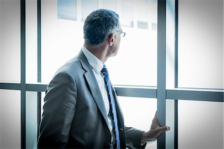 single mature people - Businessman looking out through glass wall Stock Photo - Premium Royalty-Free, Code: 649-07710045