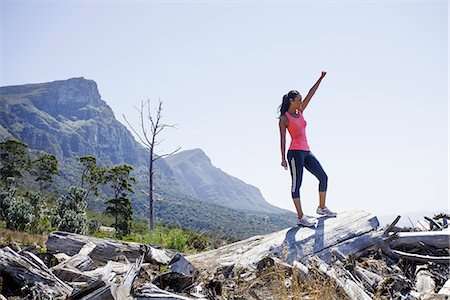 Female jogger in winning pose on hilltop Stock Photo - Premium Royalty-Free, Code: 649-07710126