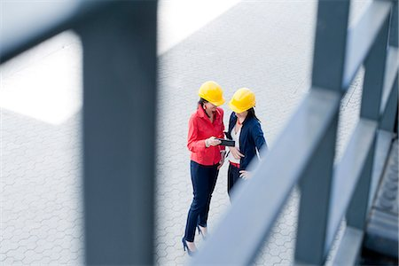 Businesswomen in safety helmet using digital tablet Stock Photo - Premium Royalty-Free, Code: 649-07710137