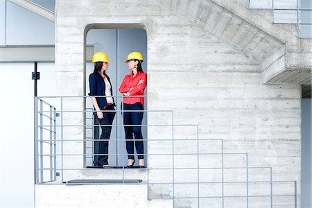Businesswomen in safety helmet at balcony Stock Photo - Premium Royalty-Free, Code: 649-07710139