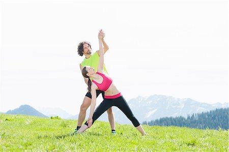 partnership - Couple practising yoga on hilltop, Wallberg, Tegernsee, Bavaria, Germany Stock Photo - Premium Royalty-Free, Code: 649-07710143