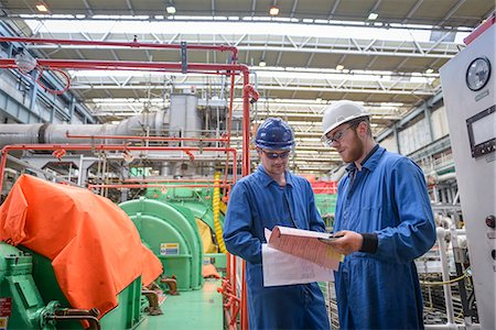 people working in factory - Engineers discussing paperwork during power station outage Stock Photo - Premium Royalty-Free, Code: 649-07710156