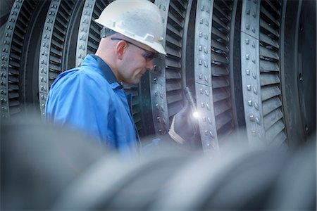 Engineer with torch inspecting turbine during power station outage Stock Photo - Premium Royalty-Free, Code: 649-07710177