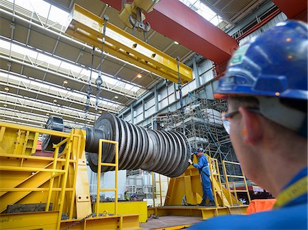 Banksman and crane operator lowering crane to turbine hall during power station outage Stock Photo - Premium Royalty-Free, Code: 649-07710172