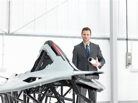 portrait - Automotive designer with part-built supercar in car factory, portrait Stock Photo - Premium Royalty-Free, Code: 649-07710245