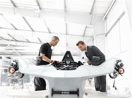 Engineer and automotive designer inspecting part-built supercar in car factory Stock Photo - Premium Royalty-Free, Code: 649-07710246
