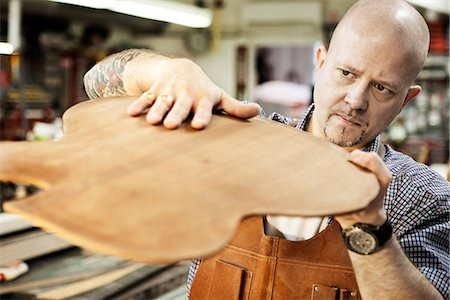 passion - Guitar maker checking wooden guitar shape in workshop Stock Photo - Premium Royalty-Free, Code: 649-07710266