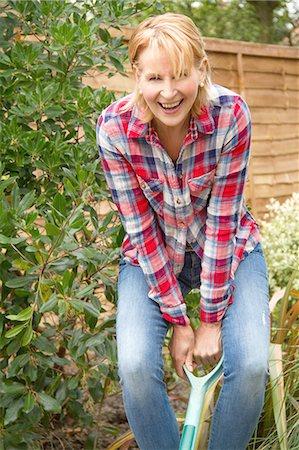 Portrait of mature woman having fun digging garden Stock Photo - Premium Royalty-Free, Code: 649-07710279